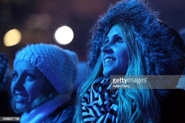 Visitors attend celebrations for the 25th anniversary of the fall of the Berlin Wall at the Brandenburg Gate on November 9 2014 in Berlin Germany The...