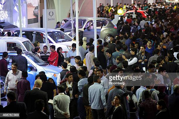 Visitors attend the Mahindra Mahindra Ltd pavilion during the 12th Auto Expo 2014 in Noida India on Friday Feb 7 2014 The motor show opens to the...