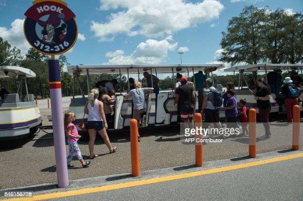 Visitors board a tram to get to Walt Disney World Resort Magic Kingdom from the parking lot in Orlando Florida on September 12 2017 two days after...