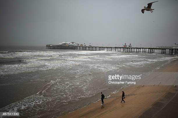 Visitors brave high winds and rain on Blackpool promenade as Britain prepares for high winds over the next two days on October 20 2014 in Blackpool...
