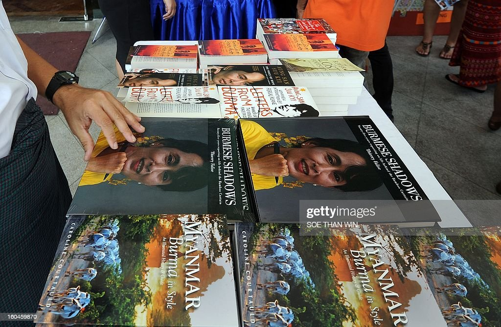 Visitors browse books on sale at a stand outside a hotel hosting Myanmar's first international literary festival, in Yangon on February 1, 2013. The Irrawaddy Literary festival opened on February 1 with a host of luminaries from the book world due to speak alongside talented local authors and event patron Aung San Suu Kyi. AFP PHOTO / Soe Than WIN