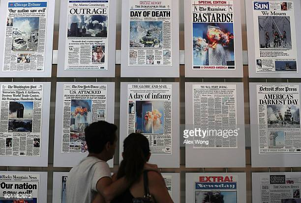 Visitors browse newspaper front pages with the story of the 9/11 terror attacks at the 9/11 Gallery of the Newseum on September 9 2016 in Washington...