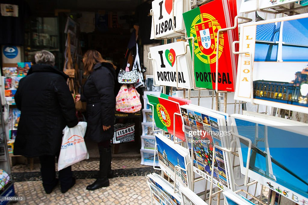 Visitors browse souvenirs for sale at at tourist store in Lisbon, Portugal, on Saturday, March 2, 2013. Prime Minister Pedro Passos Coelho is battling rising joblessness and lower demand from European trading partners as he raises taxes to meet the terms of a 78 billion-euro ($104 billion) aid plan from the European Union and the International Monetary Fund. Photographer: Mario Proenca/Bloomberg via Getty Images