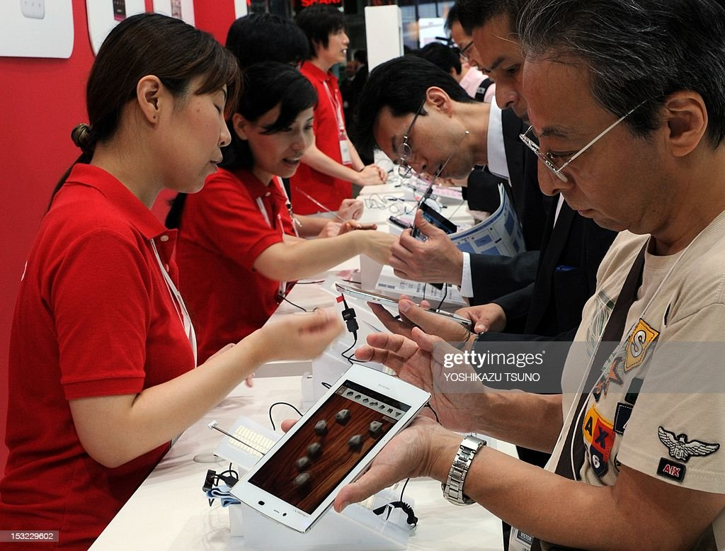 Visitors browse the latest tablets and smartphones available from Japanese mobile communication company NTT DoCoMo, at Asia's largest electronics trade show CEATEC (Cutting-Edge IT & Electronics Comprehensive Exhibition) in Chiba, suburban Tokyo on October 2, 2012. Some 600 Japanese and foreign companies exhibited their latest technology and products. AFP PHOTO / Yoshikazu TSUNO