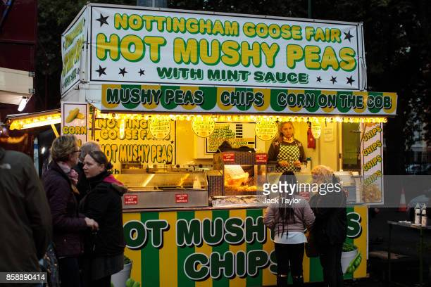Visitors buy food from a mushy peas stall at the Nottingham Goose Fair in the Forest Recreation Ground on October 7 2017 in Nottingham England The...