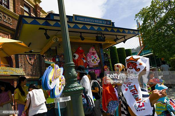Visitors buy merchandise at a store at Universal Studios Japan operated by USJ Co in Osaka Japan on Thursday Aug 7 2014 USJ is counting on its cachet...