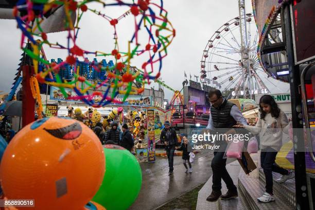 Visitors carry candy floss as they enjoy the attractions at the Nottingham Goose Fair in the Forest Recreation Ground on October 7 2017 in Nottingham...