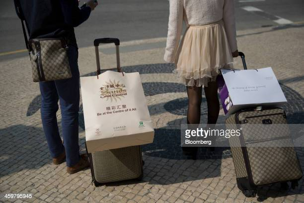 Visitors carry luggage outside the Sands Cotai Central casino resort operated by Sands China Ltd a unit of Las Vegas Sands Corp in Macau China on...