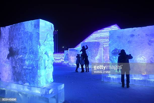 Visitors carve characters into ice as they visit the China Ice and Snow World during the Harbin International Ice and Snow Festival in Harbin...