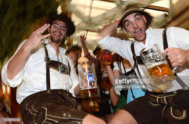 Visitors celebrate with beer mugs in a Oktoberfest beer festival tent at the Theresienwiese in Munich southern Germany on September 22 2012 This...