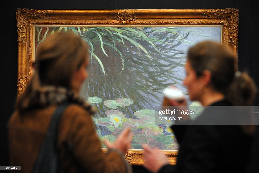Visitors chat in front of a painting entitled 'Nympheas avec reflets de hautes herbes' by French artist Claude Monet at Sotheby's auction house in central London on January 31, 2013. Due to form part of the Impressionist and Modern Art Evening Sale on February 5, it is expected to fetch between 12-18 million GBP (15-22 million EUR - 19-29 million USD).