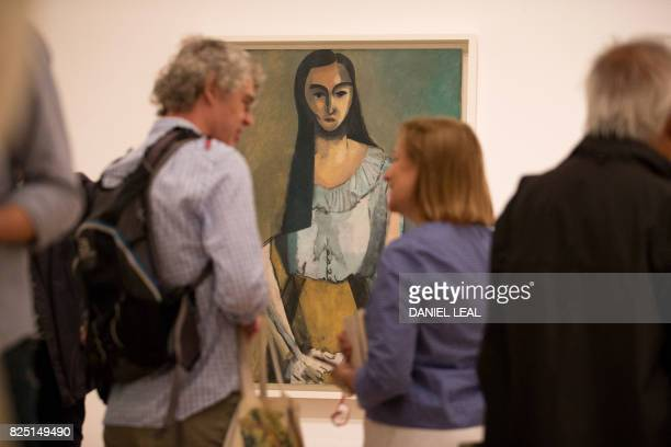 Visitors chat in front of an artwork by French artist Matisse named 'The Italian Woman during a photocall at the exhibition 'Matisse in the Studio'...