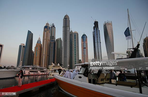 Visitors check boats docked at the Dubai International Marine Club during the Gulf emirate's international Boat Show on March 01 2106 More than 400...