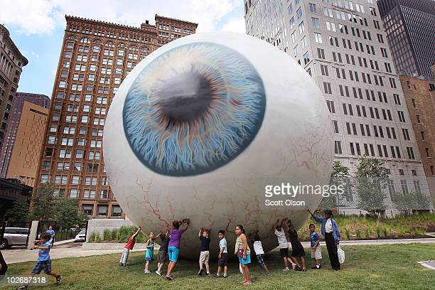 Visitors check out a 30foot tall eyeball sculpture by artist Tony Tasset following its unveiling in Prtizker Park on July 7 2010 in Chicago Illinois...
