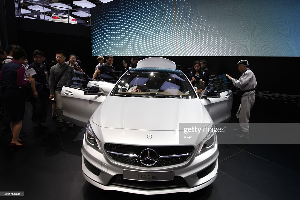 Visitors check out a Mercedes-Benz CLA-Class car on display at the China International Exhibition Center new venue during the 'Auto China 2014' Beijing International Automotive Exhibition in Beijing on April 20, 2014. Leading automakers are gathering in Beijing for the kickoff of China's biggest car show, but lackluster growth and environmental restrictions in the world's largest car market have thrown uncertainty into the mix. More than 1,100 vehicles are being showcased at the auto show, which opens to the public on April 21. CHINA OUT AFP PHOTO