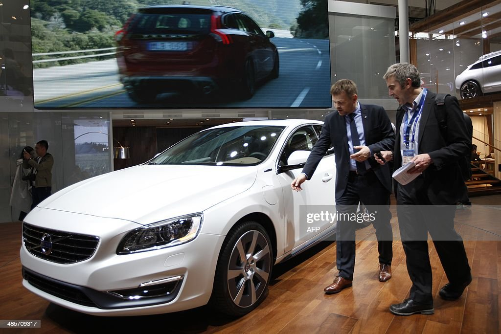 Visitors check out a Volvo car on display at the China International Exhibition Center new venue during the 'Auto China 2014' Beijing International...