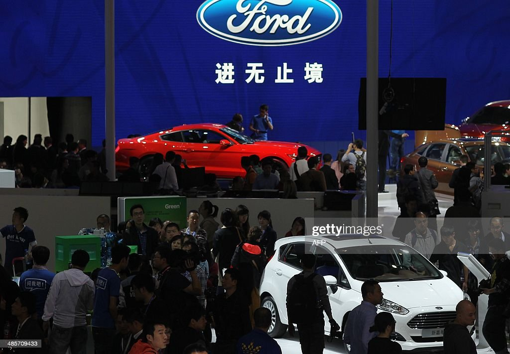 Visitors check out Ford cars on display at the China International Exhibition Center new venue during the 'Auto China 2014' Beijing International Automotive Exhibition in Beijing on April 20, 2014. Leading automakers are gathering in Beijing for the kickoff of China's biggest car show, but lackluster growth and environmental restrictions in the world's largest car market have thrown uncertainty into the mix. More than 1,100 vehicles are being showcased at the auto show, which opens to the public on April 21. CHINA