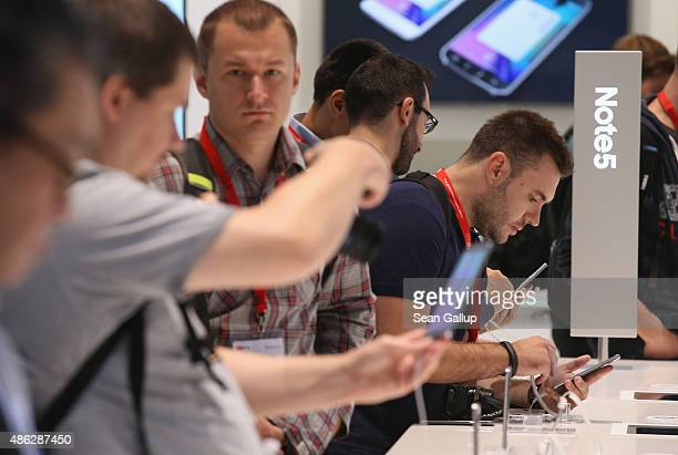 Visitors check out Galaxy Note 5 smartphones at the Samsung stand during a press day at the 2015 IFA consumer electronics and appliances trade fair...