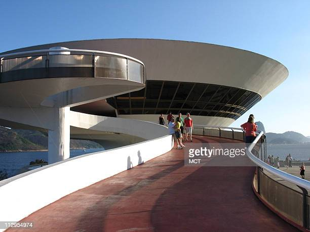 Visitors check out the distinctive Museum of Contemporary Art October 15 in Niteroi Brazil Legendary Brazilian architect Oscar Niemeyer designed the...