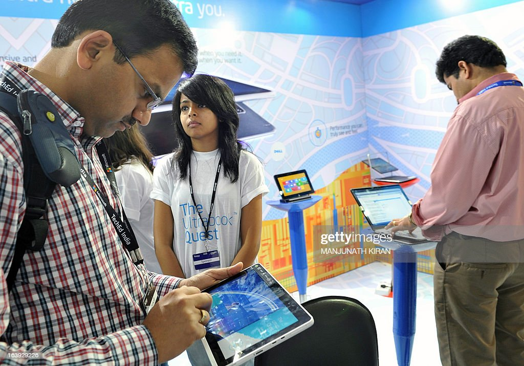 Visitors check out touchscreen laptops and tablet computing devices at an exhibition stall during the TechEd 2013 technology event in Bangalore on March 18, 2013. The technology event, organised by Microsoft, was held to empower IT professionals, entreprenuers and students with tools, technologies and training required to hone their skills in app development for the Windows platform. AFP PHOTO/Manjunath KIRAN