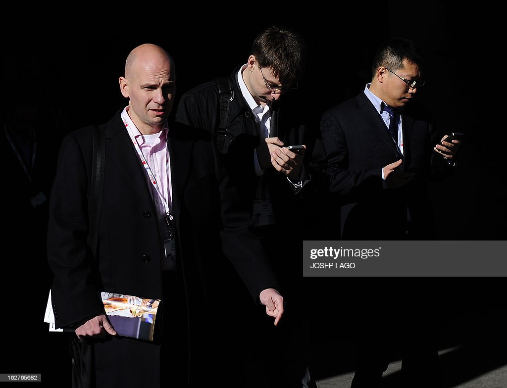 Visitors check their mobile phones at the 2013 Mobile World Congress in Barcelona on February 26, 2013. The 2013 Mobile World Congress, the world's biggest mobile fair, is held from February 25 to 28 in Barcelona.