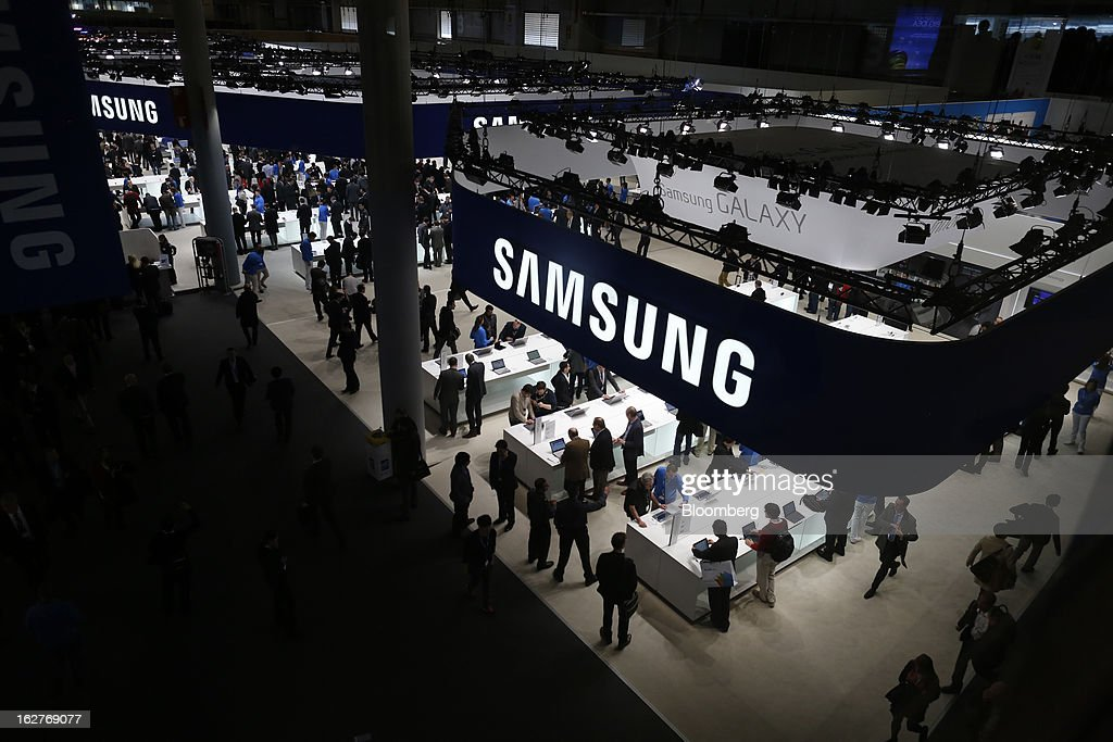 Visitors cluster around displays of mobile devices at the Samsung Electronics Co. pavilion at the Mobile World Congress in Barcelona, Spain, on Tuesday, Feb. 26, 2013. The Mobile World Congress, where 1,500 exhibitors converge to discuss the future of wireless communication, is a global showcase for the mobile technology industry and runs from Feb. 25 through Feb. 28. Photographer: Simon Dawson/Bloomberg via Getty Images