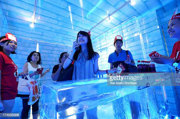 Visitors cool down in a oneday ice bar set up in a huge vending machine on July 18 2013 in Tokyo Japan The bar is to promote Japan CocaCola's...