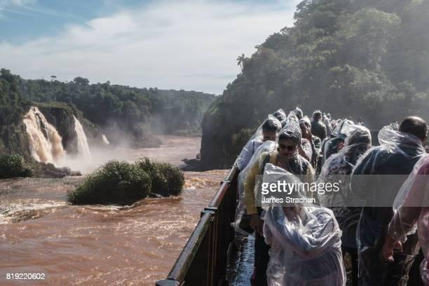 Visitors, covered in plastic clothing but still drenched in spray, walking along a walkway to the Garganta del Diablo (Devil's Throat), Iguazu Falls (UNESCO World Heritage Site) from Brazilian side, Iguazu, Brazil