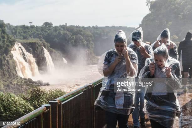 Visitors, covered in plastic clothing but still drenched in spray, walking along a walkway to the Garganta del Diablo (Devil's Throat), Iguazu Falls (UNESCO World Heritage Site) from Brazilian side, Iguazu , Brazil