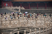 Visitors crossing one of the bridges in the Forbidden City Beijing China The Forbidden City was the Chinese imperial palace from the Ming Dynasty to...