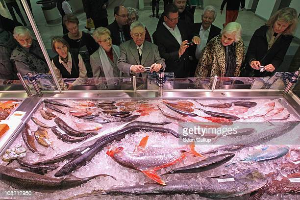 Visitors crowd a display of fresh fish at a stand at the 2011 Gruene Woche international agricultural trade fair at Messe Berlin on January 21 2011...