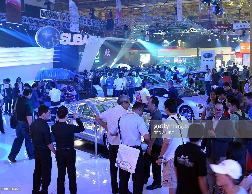 Visitors crowd around cars on display at the auto show in Manila on April 4, 2013. The annual auto show is being held from April 4 to 7 at the world trade center.