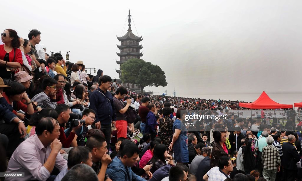 Visitors crowd to watch the soaring tide of the Qiantang River on October 6, 2017 in Hangzhou, Zhejiang Province of China. When the surging tide comes, around 110,000 visitors flock there to watch it.