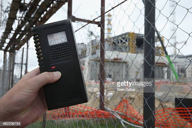 A visitor's dosimeter shows a radiation reading of just under one microsievert per hour which is still considered safe outside the encased remains of...