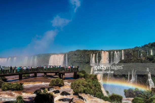 Visitors, drenched in spray, on walkway in the middle of the Garganta del Diablo (Devil's Throat), Iguazu Falls (UNESCO World Heritage Site) from Brazilian side, with rainbow in right foreground, Iguazu, Brazil