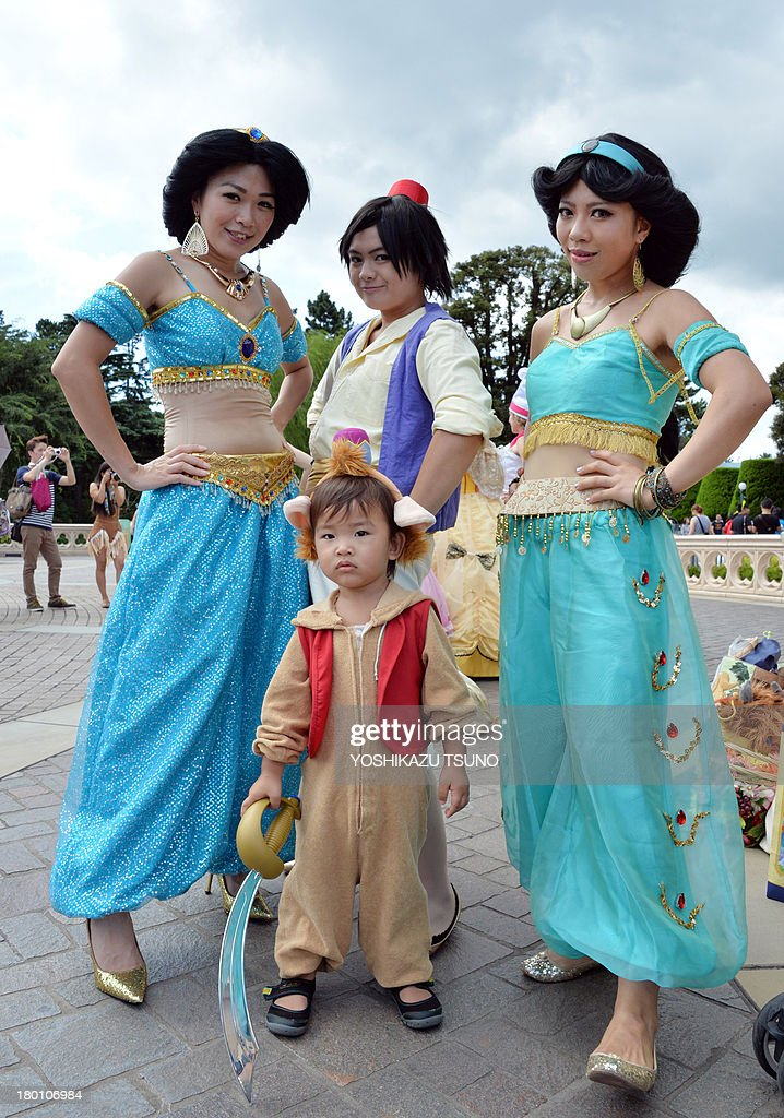 Visitors dressed in costumes from Disney's animated movie 'Aladdin' pose for photos at Tokyo Disneyland in Urayasu, suburban Tokyo on September 9, 2013. Tokyo's Disney theme park runs Halloween events through till October 31 and visitors are allowed to wear Disney related costumes in the park. AFP PHOTO / Yoshikazu TSUNO