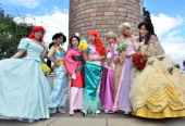 Visitors dressed in costumes of Disney princesses pose for photos at Tokyo Disneyland in Urayasu suburban Tokyo on September 9 2013 Tokyo's Disney...