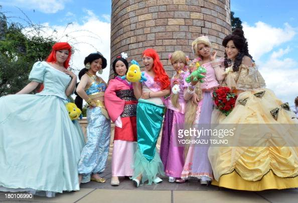 Visitors dressed in costumes of Disney princesses pose for photos at Tokyo Disneyland in Urayasu suburban Tokyo on September 9 2013 Tokyo's Disney...