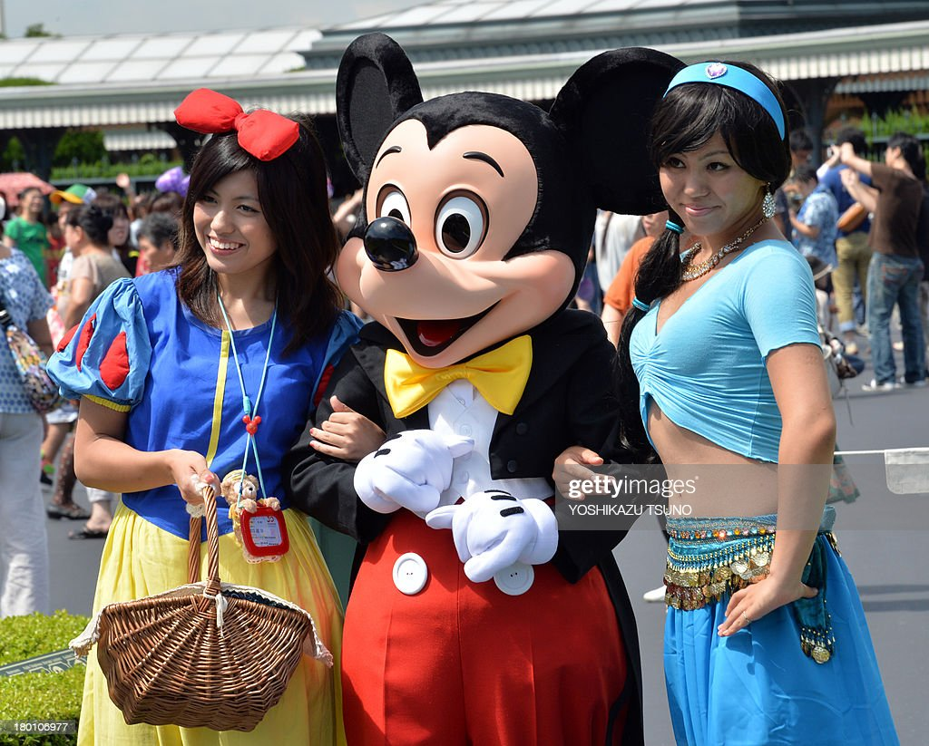 Visitors dressed in costumes of Snow White (L) and Jasmine (R) smile as they pose with Mickey Mouse (C) at Tokyo Disneyland in Urayasu, suburban Tokyo on September 9, 2013. Tokyo's Disney theme park runs Halloween events through till October 31 and visitors are allowed to wear Disney related costumes in the park. AFP PHOTO / Yoshikazu TSUNO