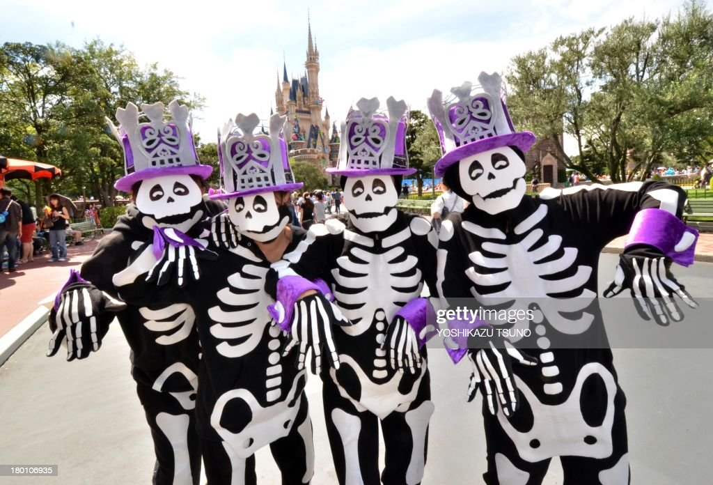 Visitors dressed in skeleton costumes to mark the upcoming Halloween pose before the castle at Tokyo Disneyland in Urayasu, suburban Tokyo on September 9, 2013. Tokyo's Disney theme park runs Halloween events through till October 31 and visitors are allowed to wear Disney related costumes in the park. AFP PHOTO / Yoshikazu TSUNO
