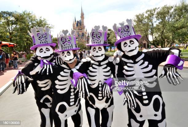 Visitors dressed in skeleton costumes to mark the upcoming Halloween pose before the castle at Tokyo Disneyland in Urayasu suburban Tokyo on...
