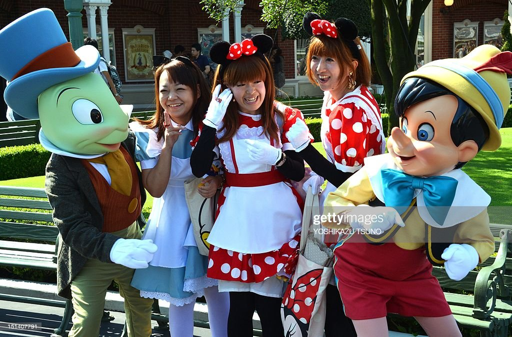 Visitors dressed in teh costumes of Alice and Minnie Mouse smile with Pinocchio and Jiminy Cricket mascots at the Tokyo Disneyland in Tokyo on...