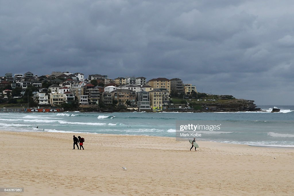 Visitors dressed in winter clothing to combat the cold temperatures are seen as a surfer walks to the surf at Bondi Beach on June 27, 2016 in Sydney, Australia. Sydney experienced its coldest day of the year on Sunday, and more icy weather is forecast for later in the week when a second cold front hits later in the week.