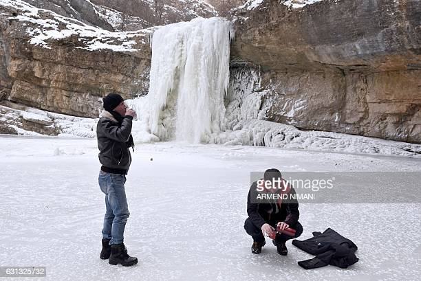Visitors drink coffee at the frozen waterfalls of Mirusha near the village of Lapceve on January 9 2017 as temperatures dropped to minus 20 C in...