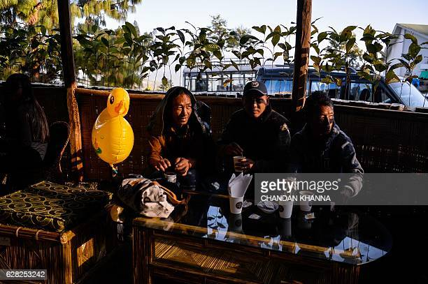 Visitors drink Naga coffee at the annual Hornbill Festival at Kisama village some 15 kms from Kohima capital of the northeastern state of Nagaland on...