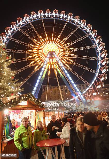 Visitors eat sausages among stalls as a ferris wheel spins behind at the annual Christmas market at Alexanderplatz on the market's opening day on...