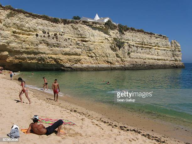 Visitors enjoy a beach on the Algarve coast on July 30 2008 near Armacao de Pera Portugal Portugal is becoming an increasingly popular tourist...