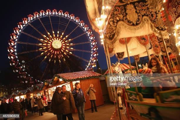 Visitors enjoy a meerygoround at the Christmas market at Alexanderplatz square under an illuminated ferris wheel on November 26 0213 in Berlin...