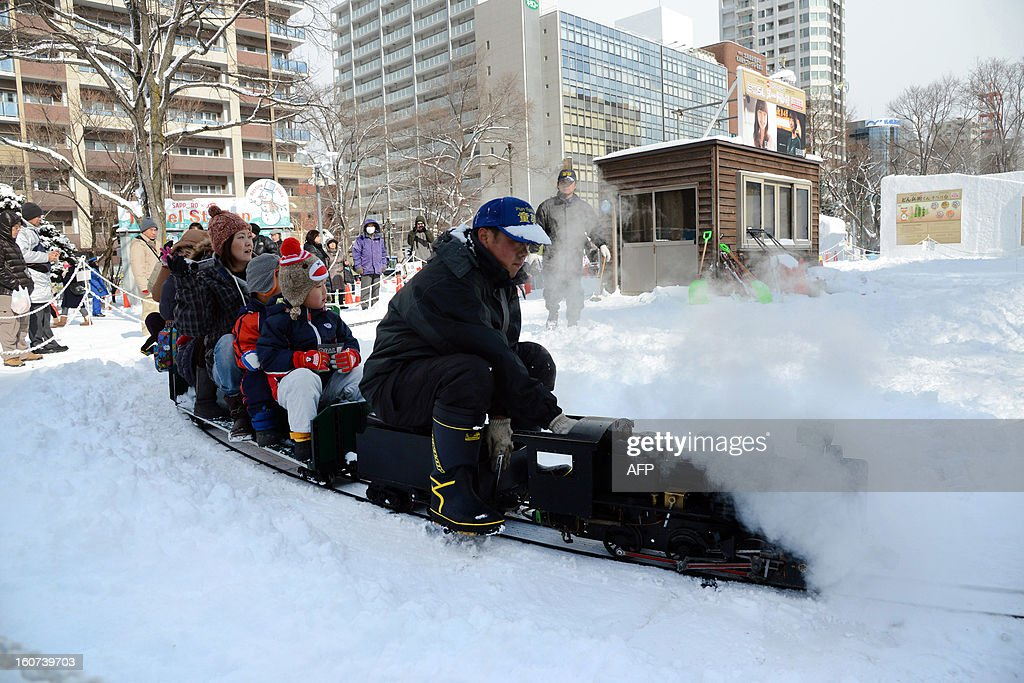 Visitors enjoy a ride on a scale model of a steam locomotive at the opening of the annual snow festival in Sapporo, on Japan's northern island of Hokkaido on February 5, 2013. Some two million people are expecting to visit the week-long festival which has over 200 snow sculptures. AFP PHOTO / TAKASHI NOGUCHI