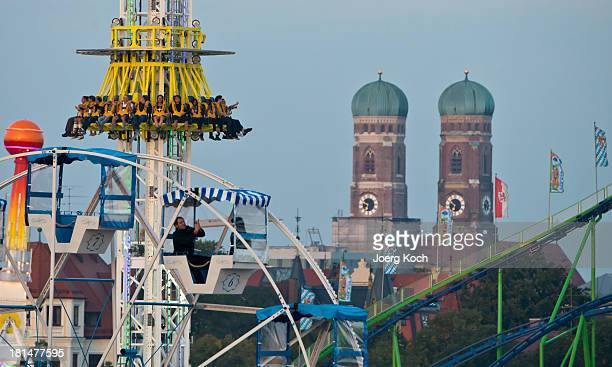Visitors enjoy amusement rides in front of the famous backdrop of Munich Frauenkirche at the Oktoberfest 2013 beer festival at Theresienwiese on...